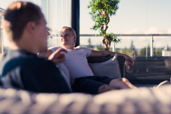 Miehet istuvat terassilla auringossa.
