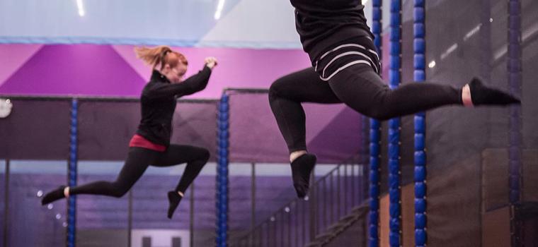 Ihmisiä hyppimässä trampoliinilla.