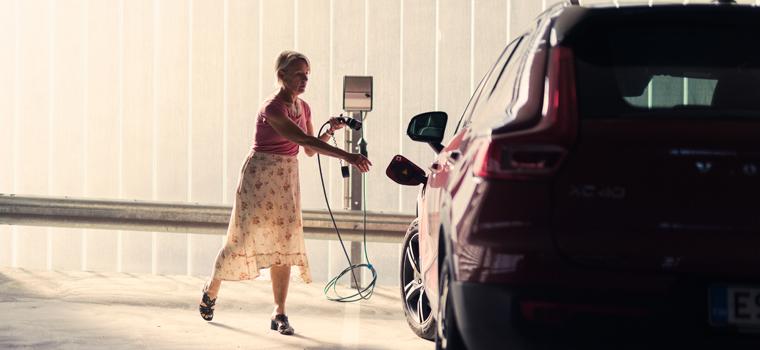 Nainen laittamassa sähköautoa lataukseen parkkihallissa.